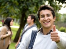 Happy male student with thumbs up outdoors