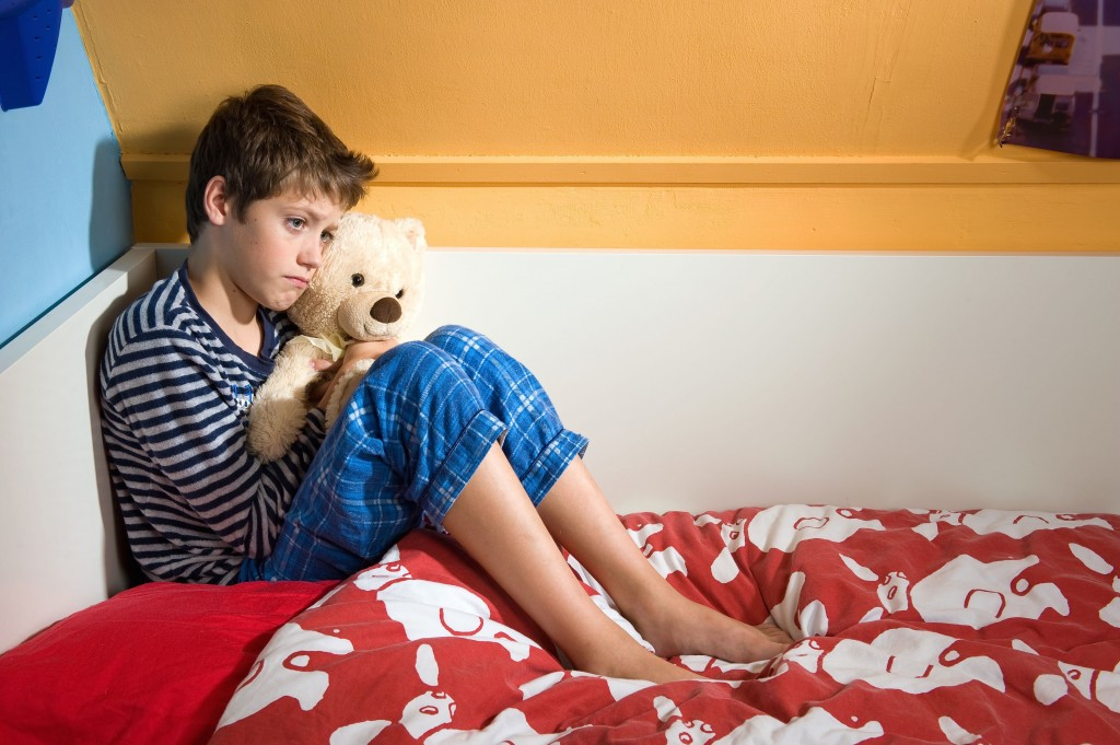 A young boy is sitting sad and depressed on his bed in his bedroom