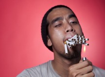 Young smoker burn cigarettes using a match