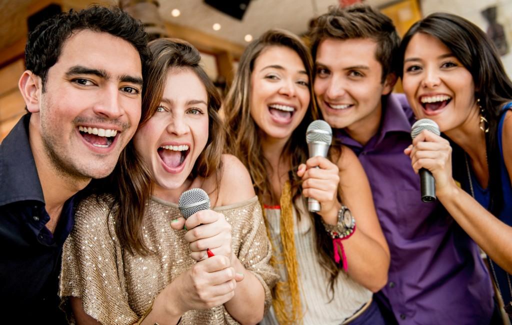 Group of friends karaoke singing at the bar