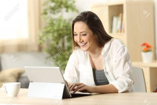 Casual happy woman writing e mail in a tablet pc on line sitting in a desk at home with a homey background