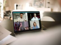 Business people having online meeting. Group of men and woman having a video conference over a laptop.