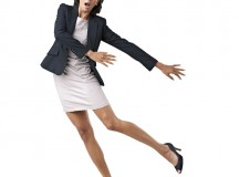 Accident-prone female executive falling over against a white background